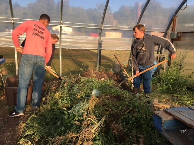 students cleaning the hoophouse