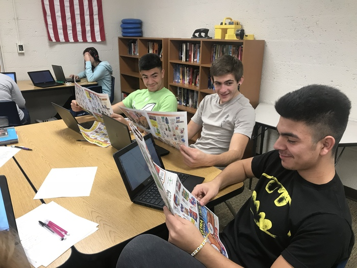 students reading grocery ad